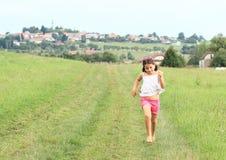 Little girl running barefoot Stock Photography
