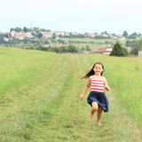 Little girl running barefoot Stock Photos