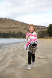 Little girl running on beach Stock Image