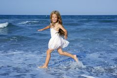 Little girl running beach in blue sea Royalty Free Stock Photos