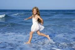 Little girl running beach in blue sea Royalty Free Stock Photos