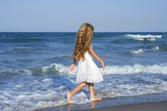 Little girl running beach in blue sea Royalty Free Stock Images