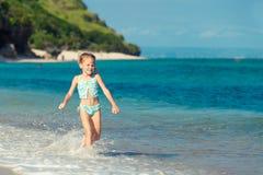 Little girl running on the beach Stock Images