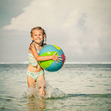 Little girl running on the beach Stock Image