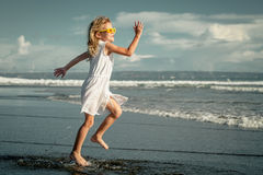 Little girl running on the beach at the day time Royalty Free Stock Images