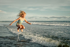 Little girl running on the beach at the day time Stock Photo