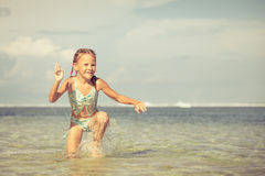 Little girl running on the beach at the day time Royalty Free Stock Photography