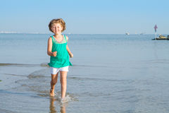 Little girl is running on the beach with her feet in the sea Royalty Free Stock Photos
