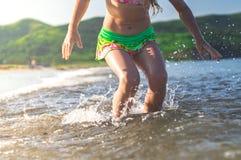 girl running beach shore splashing water in blue sea Stock Photo