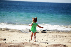 Little girl running on beach Stock Photography