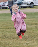 Little girl running. Little blonde haired girl wearing orange rubber boots running Stock Photos
