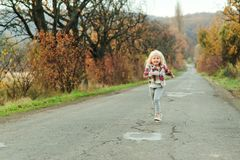 Little girl running down the road in autumn time. Happy child girl with long hair outdoors. Autumn holidays. Happy childhood. Autumn season. Walking on nature royalty free stock image