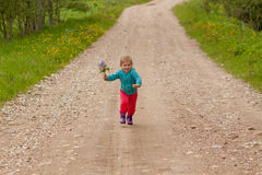 Little girl running down the road Stock Photography