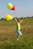 Little girl running on field. With balloons Stock Photography