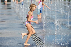 Little girl running among fountains Stock Photo