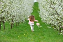 Little girl running in the garden Royalty Free Stock Images