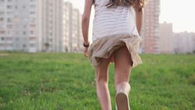 Little girl running on grass on city lawn in summer day stock footage