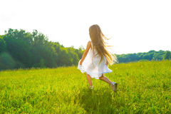 Little girl running on green grass. Royalty Free Stock Image