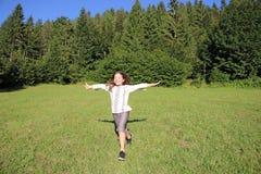 Little girl running on green grass field Royalty Free Stock Image