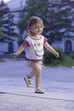 Little girl running. Happy girl 2-3-4 years old with braids running down the road in the park Stock Photography