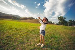 Little girl running with kite happy and smiling on summer field.  Royalty Free Stock Images