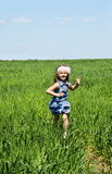 Little girl running on a meadow Stock Photo