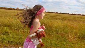 Little girl running on meadow with sunset. Toned. girl kid runs along the rural road slow motion video. little girl with stock video footage