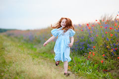 A little girl running near the field. The joy on the face of the Royalty Free Stock Photos
