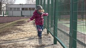Little Girl Running Next to Metal Grid. 4k Ultra HD stock video footage