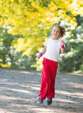 Little girl running in park Stock Images