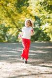Little girl running in park Stock Photos