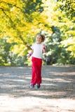 Little girl running in park Stock Image