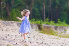 Little girl running in a pine forest Stock Photo