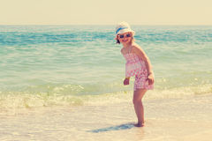 Little girl running and playing on the beach. The image is tinte Royalty Free Stock Image