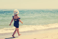 Little girl running and playing on the beach. Stock Images