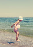 Little girl running and playing on the beach. Royalty Free Stock Image