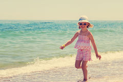 Little girl running and playing on the beach. Royalty Free Stock Photos