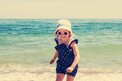 Little girl running and playing on the beach. Stock Photo