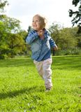 Little girl running and playing outdoors. Portrait of a little girl running and playing outdoors stock photography