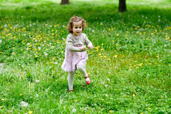 Little girl running and playing in the park Stock Images