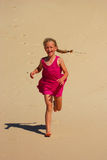 Little girl running in sand stock photos