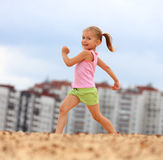 Little girl running in sand Stock Image