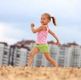 Little girl running in sand Stock Image