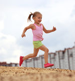 Little girl running in sand Stock Images