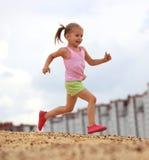 Little girl running in sand stock images