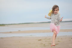 Little girl running on sand against sea and sky Stock Photos