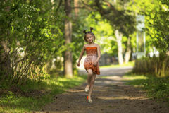 Little  girl running skipping through the Park. Stock Image