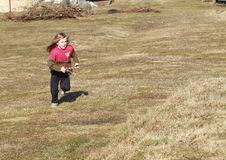 Little girl running with a sling-shot Royalty Free Stock Photography