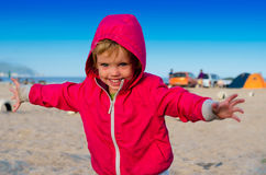 Little girl running and smiling near the camping tents on the se Royalty Free Stock Photography