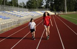 Little girl running on the stadium with a coach royalty free stock photography
